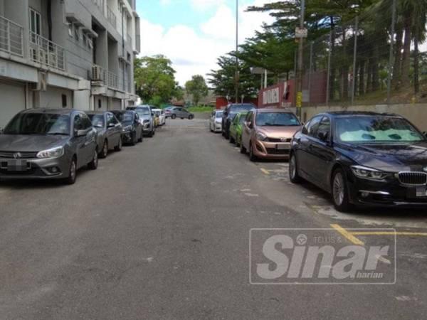 Kereta yang diparkir di kiri kanan jalan di belakang Dataran Mutiara menyukarkan kenderaan lain untuk lalu.