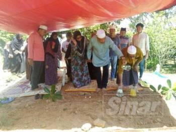Mahdzir menjirus air mawar ke atas pusara ibunya di Tanah Perkuburan Islam Surau al-Islamiah Kampung Lancuk Emat, Mukim Bukit Lada di sini hari ini.