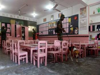 Anggota unit pemusnah bom Sri Lanka menggunakan anjing pengesan ketika memeriksa sebuah sekolah di Colombo, semalam. - Foto AFP