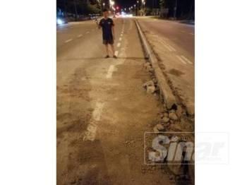 Teck Keng meninjau kerosakan pembahagi jalan akibat dirempuh kenderaan baru-baru ini.