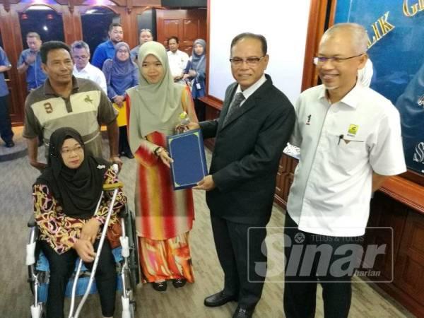Nur Aqilah Atikah teruja menerima biasiswa BKMB tersebut daripada Wan Rosdy di Wisma Pahang di sini hari ini.
