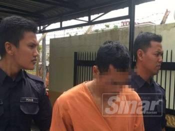 Suspek (tengah) ketika dibawa keluar dari Mahkamah Majistret Tanah Merah.