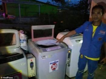 Anggota penyelamat menunjukkan mesin basuh di mana bayi itu ditemukan.
