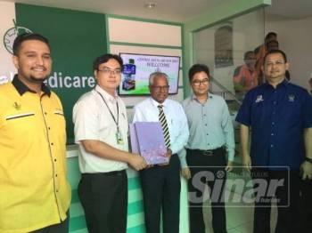 Sivanesan (tengah) menerima cenderahati daripada pihak kilang selepas lawatannya di sini, hari ini.