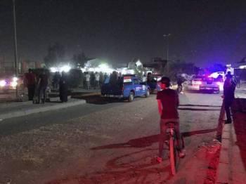 Pasukan keselamatan Iraq dan orang awam berkumpul di lokasi serangan bom bunuh diri di Baghdad semalam. - FOTO AP