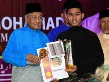 Dr Mahathir merangkap Yang Dipertua Perkim menyampaikan Anugerah Kepimpinan Cemerlang Kelab Perkim Universiti kepada Muhammad Sabhan Iman Ismail dari Universiti Islam Antarabangsa Malaysia pada majlis iftar hari ini. -Foto Bernama