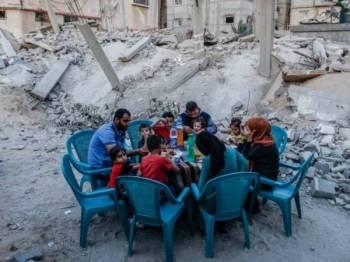 Sebuah keluarga Palestin di Rafah berbuka puasa bersebelahan rumah mereka yang musnah akibat pertempuran antara Hamas dan Israel.