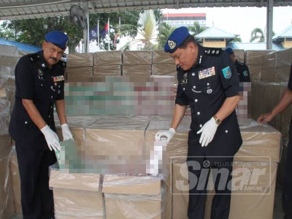 Paul (kanan) bersama Pegawai PPM W2 Muar, Deputi Superintendan Nordin Osman menunjukkan karton rokok yang disimpan dalam sebuah kotak.