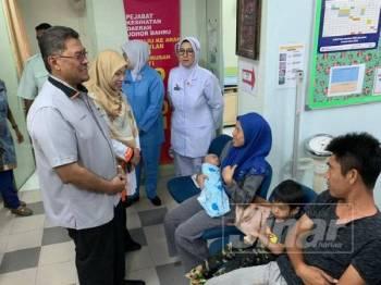 Dzulkefly (kiri) beramah mesra bersama salah seorang pengunjung Klinik Kesihatan Kampung Paya Mengkuang di sini hari ini.