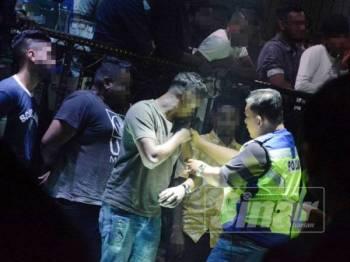 Pegawai polis melakukan pemeriksaan tatoo pada anggota badan pengunjung bagi mengenal pasti mereka yang terlibat dengan aktiviti kongsi gelap.