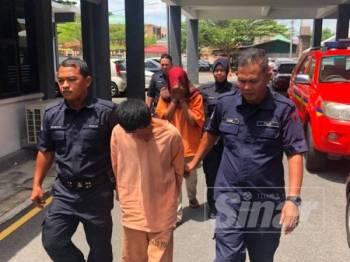 Tertuduh Mohd Hafiz Abdullah, 31, (tengah) dan isterinya, Farah Nasuha Razali, 28, (belakang) dikawal ketat polis keluar dari Mahkamah Sesyen Kota Bharu selepas dihukum atas kesalahan mendera tiga anak mereka.