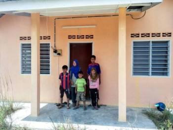 Pasangan suami isteri Auseng Ngoh, 35, (kanan) dan Haida Abdullah, 32, bersama tiga anak mereka Muhamad Hafiz Haika, 12, Nur Asyikin, 11, dan Muhammad Syawal Fitri, 7, di hadapan rumah baharu mereka sumbangan Majlis Agama Islam Kelantan (MAIK) di Kampung Tanah Puteh, Gua Musang hari ini. - FOTO BERNAMA
