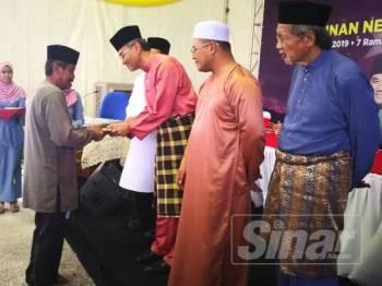 Menteri Kesihatan, Datuk Seri Dr Dzulkefly Ahmad menyampaikan sumbangan kepada penerima sambil diperhatikan Amirudin pada Majlis Iftar Perdana Bersama Pemimpin di Kampung Bukit Badong semalam.