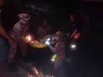 Anggota bomba membawa keluar mayat mangsa yang ditemui di celahan batu selepas dipercayai terjatuh ketika memancing di pantai Teluk Batik, semalam. -Foto Ihsan Bomba
