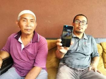 Adik kepada Mohd Mudakir, Hairuzaman (kanan) menunjukkan rakaman video yang tular di media sosial melibatkan abangnya itu.