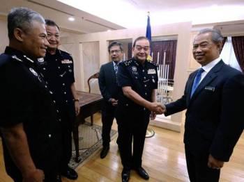 Menteri Dalam Negeri Tan Sri Muhyiddin Yassin (kanan) bersalaman dengan Timbalan Ketua Polis Negara yang baharu Datuk Mazlan Mansor (dua, kanan) ketika menerima kunjungan hormat Timbalan Ketua Polis Negara di Kementerian Dalam Negeri hari ini. - Foto Bernama