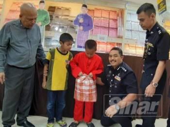 Mohd Ali (tengah) membantu mengenakan pakaian kepada salah seorang anal yatim di gedung Jakel hari ini.