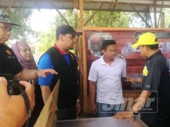 Syeikh Azhari (kanan) menasihatkan seorang pemuda yang tidak sempat melarikan diri ketika serbuan di Mergong, di sini, hari ini.