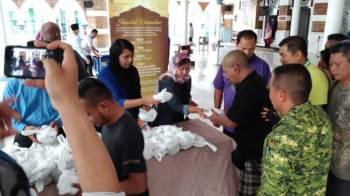 Susan (tengah) bersama wakil pengurusan Masjid Jamek Sultan Abdul Samad mengedarkan bubur lambuk kepada golongan asnaf dan gelandangan.