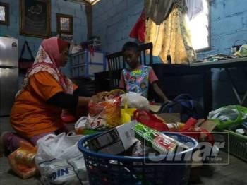 Nor Azila mengemas barang sumbangan orang ramai untuk anak saudaranya.