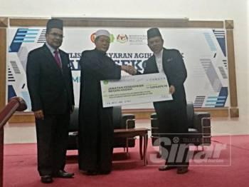 Syeikh Fadzil (tengah) menyerahkan cek agihan balik zakat kepada Mohd Syauqi (kanan) sambil diperhatikan Syeikh Zakaria (kiri) dalam Majlis Penyerahan Pembayaran Agihan Balik Zakat Sekolah Seluruh Kedah di Maktab Mahmud Alor Setar hari ini.