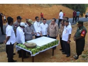 Presiden Jokowi bersama beberapa pegawai melihat peta ketika melakukan lawatan ke Gunung Mas di Kalimantan Tengah pada 8 Mei lalu. - Foto Antara