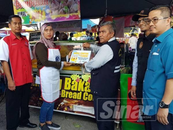 Mohd (tiga dari kanan), Ahmad Nazwawi (kanan) dan Mohd Anuar (dua dari kanan) menyampaikan Anugerah Gerai Contoh kepada peniaga di Bazar Ramadan Jalan Padang sempena pelancaran Kempen Kebersihan dan Keselamatan Makanan Bazar Ramadan.