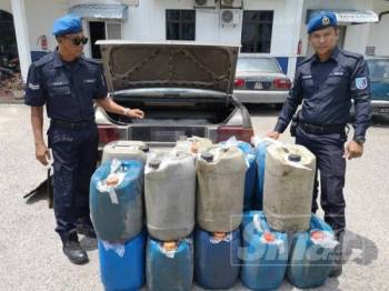 Anggota PPM Pengkalan Kubor menunjukkan diesel dan petrol yang dirampas.