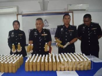 Mohd Said (dua kiri) menunjukkan air ketum botol sejuk beku yang dirampas pada sidang media petang tadi.