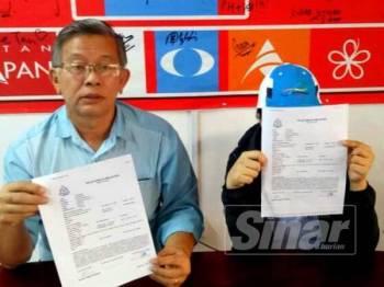 Meng (kanan) dan Seh Yong menunjukkan laporan yang dibuat di Ibu Pejabat Polis Daerah Seremban.