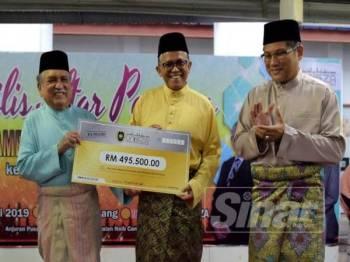 Dr Hassan Basri (tengah) menerima replika berjumlah RM495,500 daripada Dr Muhammad Nur.