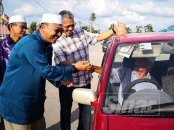 Abd Rahman (kiri) bersama kepimpinannya beramah-mesra bersama penduduk pada Majlis Pemberian Bubur Lambuk di Pekan Bagan Terap di sini.