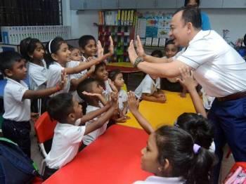 Dr Maszlee (kanan) beramah mesra dengan murid-murid sekolah ketika melakukan lawatan di Sekolah Jenis Kebangsaan Tamil (SJKT) Sungai Ara, hari ini. - Foto Bernama
