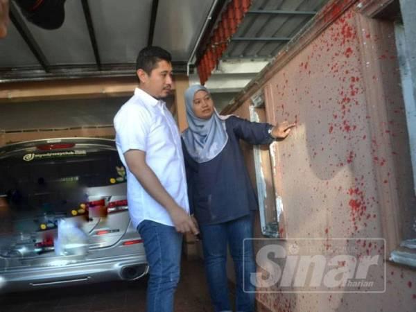 Norhayati menunjukkan kesan cat dibaling ke dinding rumahnya kepada Hilman, dalam kejadian ancaman baru-baru ini.