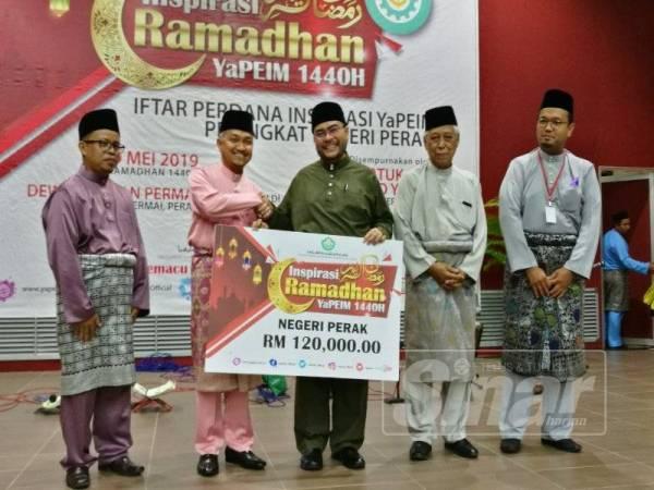 Mujahid (tiga, kiri) menerima cek replika sumbangan YaPEIM untuk pelajar negeri Perak bernilai RM120,000 daripada Mohd Zamri (dua, kiri) dalam majlis iftar perdana Inspirasi YaPEIM negeri.