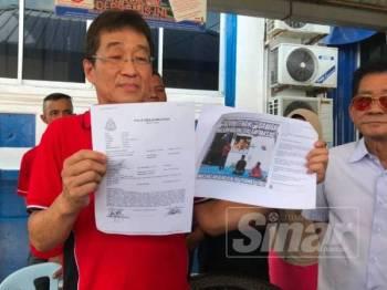 Hok Liong menunjukkan laporan polis yang dibuatnya semalam di Ibu Pejabat Polis Daerah Segamat.