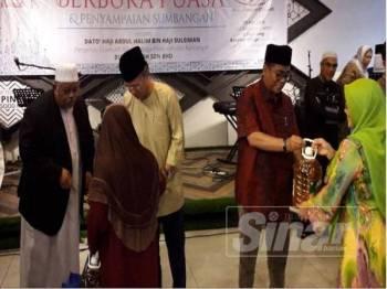 Mohamed Khaled (kanan) ketika menyampaikan sumbangan kepada penerima dalam Majlis Berbuka Puasa dan Penyampaian Sumbangan Bukti Megah Sdn Bhd di Restoran Banafee Seri Alam.