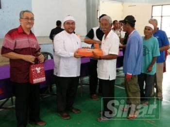 Mujahid (dua dari kiri) menyerahkan sumbangan Aidilfitri kepada penduduk di kawasan Tanjung Piandang di Dewan MPKK Tanjung Piandang hari ini.