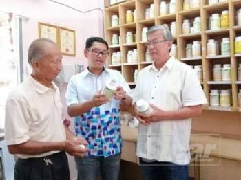 Ahmad Faizal (tengah) melihat bekalan ubat yang terdapat di Pusat Pemeriksaan Kesihatan Persatuan Penganut Agama Buddha Temoh.