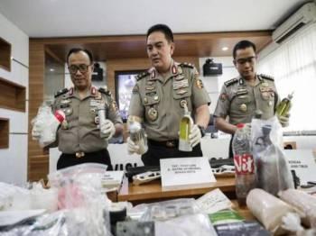 Muhammad Iqbal (tengah) menunjukkan bahan bukti yang dirampas ketika sidang media di Jakarta semalam.