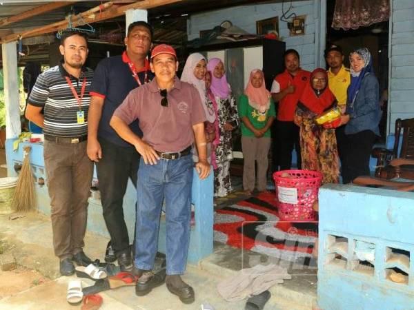 Misnah (tiga dari kanan) menerima sumbangan daripada Risda Batu Pahat di rumahnya di Tongkang Pechah semalam.