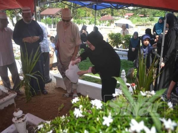 Mahamed (dua, kanan) semasa pengebumian jenazah Adam di Tanah Perkuburan Islam Lemal.