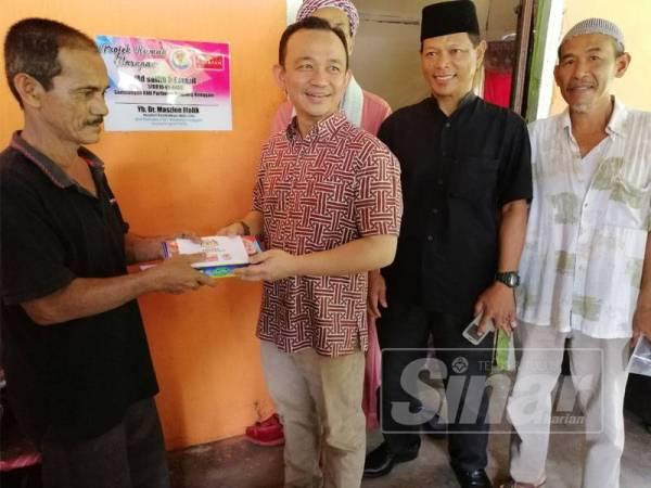 Maszlee (tiga, kanan) menyerahkan sumbangan kepada penerima bantuan di Kampung Parit Haji Hashim, Simpang Renggam.