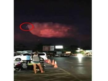 Sebuah objek berwarna putih keluar dari kepulan awan besar berwarna merah.