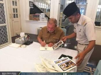 Sultan Ibrahim sedang menurunkan tanda tangan pada kad raya. - Foto ROYAL PRESS OFFICE