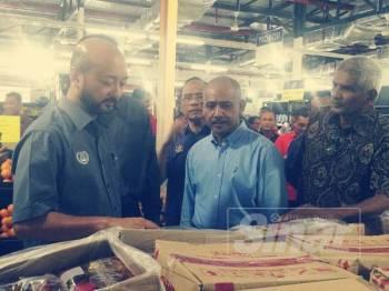 Mukhriz (kiri) meninjau barangan keperluan asas di sebuah pasaraya di Batu 5 Sik yang menggunakan sistem kad KIDA.