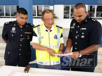 Omar Bakhtiar(tengah) meneliti kandungan laporan soal-siasat kedua suspek ditahan berhubung kes kemalangan kereta 'sardin' membabitkan 16 penumpang di Bukit Merah, semalam.