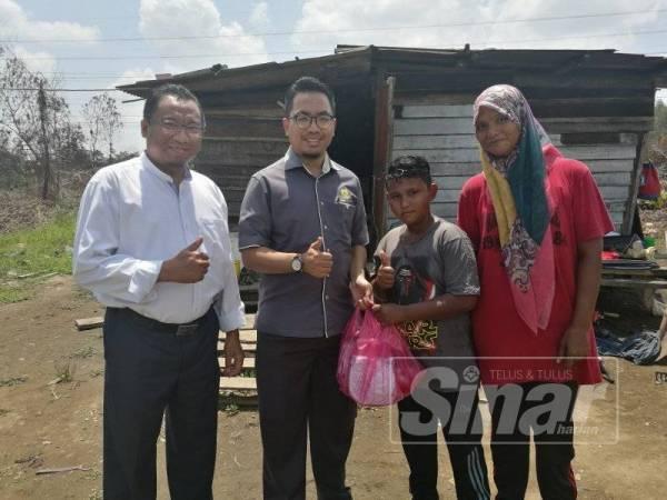 Mohd Shukri (dua, kanan) bersama ibunya, Nor Azuha menerima murtabak ferry yang disampaikan oleh Mohd Aminur (dua, kiri) diiringi Mohd Rashimi ketika menemui keluarga tersebut di rumahnya di Permatang Badak di sini, hari ini.