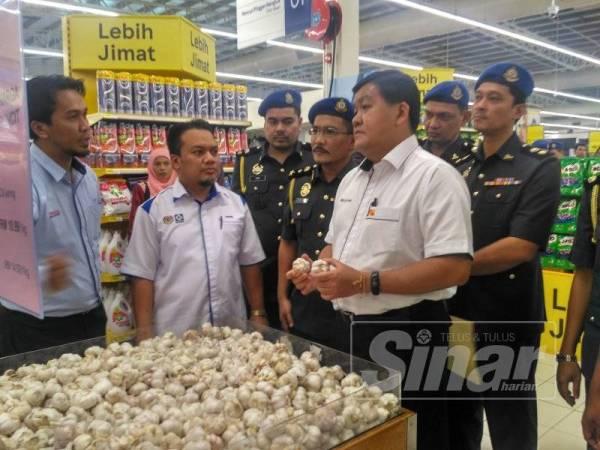 Loy Sian (dua dari kanan) bersama Zikril (dua dari kiri) meninjau harga barangan selepas pelancaran SHMMP di Tesco Extra Bukit Puchong hari ini