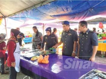 Mohd Faizul (dua dari kanan) memeriksa bazar Ramadan di Jerantut baru-baru ini.